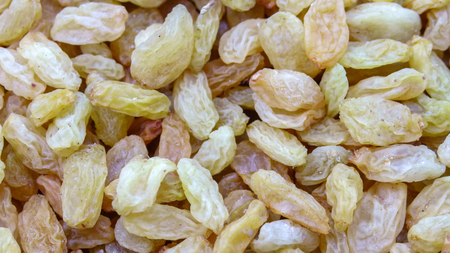 Dried white grapes pitted, raisins closeup background