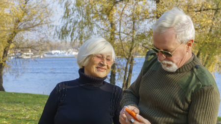 Portrait of a loving elderly couple with a smartphone in hand on the background of the autumn city park