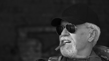 Portrait of confident elderly man wearing protective clothing in sunglasses with a cigar against the background of old concrete walls