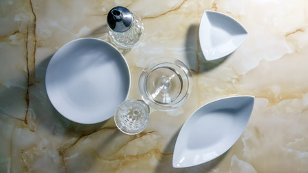 Still life with white dining utensils, glasses on a marble countertop Stock Photo