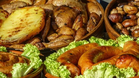 Potatoes, mushrooms champignons and grilled sausages in a bowl close up Stock Photo