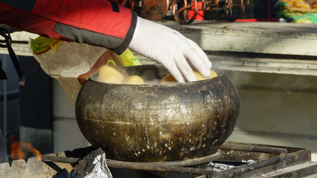 Preparation of boiled potatoes in a castiron bowl over an open fire at a picnic close up