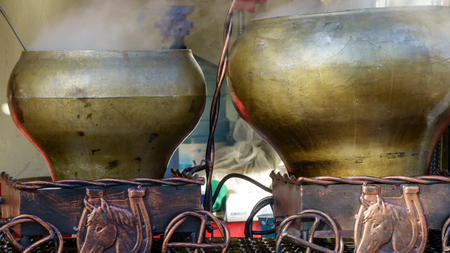 Preparation of boiled potatoes in a cast-iron bowl over an open fire at a picnic close up Stock Photo