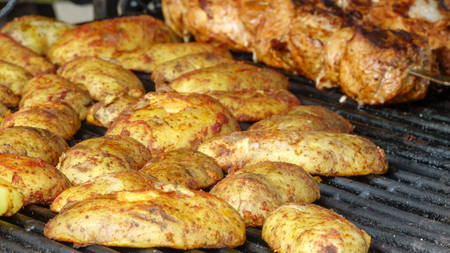 Grilled potatoes and meat on the stove close up Stock Photo
