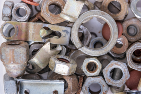 Metal nuts of different diameters, new and old, used in close-up Stockfoto