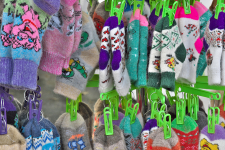 Hand-woven woolen and down socks and gloves hang on a clothesline on clothespins close-up