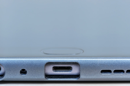 Micro connectors and holes for sound speakers and microphone of a modern smartphone close-up macro