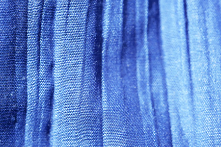 Blue background of fabric weaving cotton threads close-up macro shot