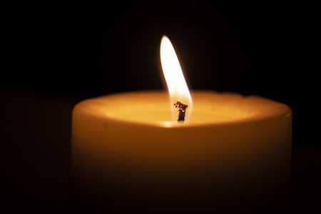 A large thick candle burns on a window sill in front of a window at night, close-up macro photography Stock Photo