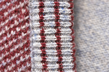 Knitted machine knitted fabric close-up, sweater element macro photo colored background Фото со стока