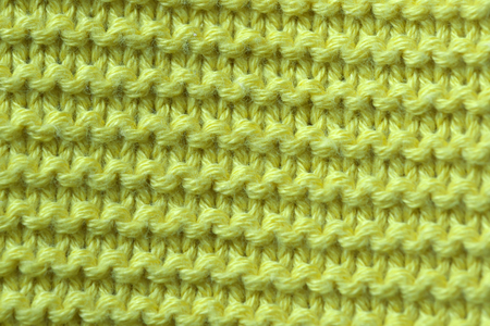 Knitted woolen fabric of a machine large knitting close-up, an element of a woman's dress macro photo yellow background