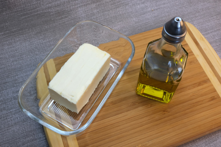 A small bottle of olive oil and glassware with butter on the table with a gray tablecloth Banco de Imagens