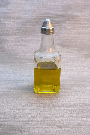 A small bottle of olive oil on the table with a gray tablecloth