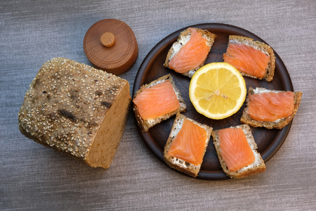 Mini sandwiches with butter and salmon on a brown clay plate Banco de Imagens