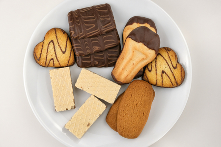 Assorted shortbread dough biscuits with chocolate on a white plate photography from above close-up on a white background