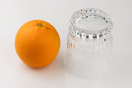 One fresh ripe citrus fruit orange next to an empty upside-down glass on a white background close-up