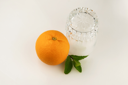 One fresh ripe citrus fruit orange next to an empty upside-down glass on a white background close-up Stock Photo