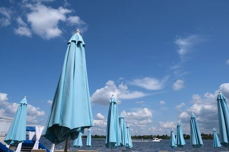 Blue closed stationary beach umbrellas and sun loungers on a sandy beach on the bank of a river without people having a rest on a bright summer day against a cloudy sky