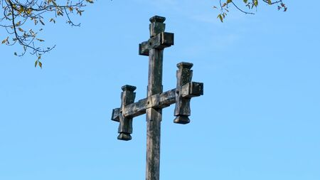 Old wooden christian roadside cross on a bright sunny day