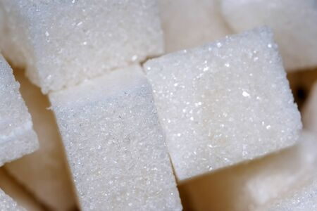 Pieces of refined sugar lie in a glass saucer, close-up, macro photo