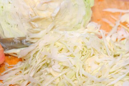 Shredder cabbage for pickling with carrots and spices in a glass jar in a city apartment, close-up Standard-Bild
