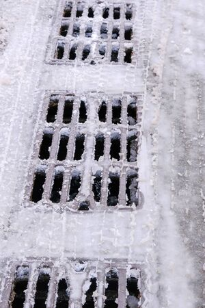 Metal grills blocking the entrance to the city storm sewers in winter, melting snow, close-up Stockfoto