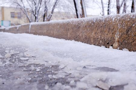 Paved road covered with melting snow in poor condition in a city courtyard winter study, close-up