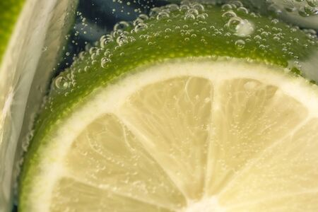 Slices of lime in a glass of soda water close-up macro photography product background