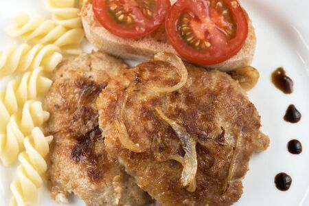 Tasty fresh hot meat cutlet from a mix of beef, pork and chicken fried with onions close-up with a slice of white bread and a tomato with pasta on a white plate macro photo