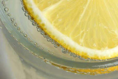 Round lemon slice in slaked soda water, refreshing lemonade close-up macro photography food vegetarian background