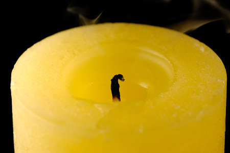 Extinguished thick commemorative yellow candle on a black background close-up macro photography