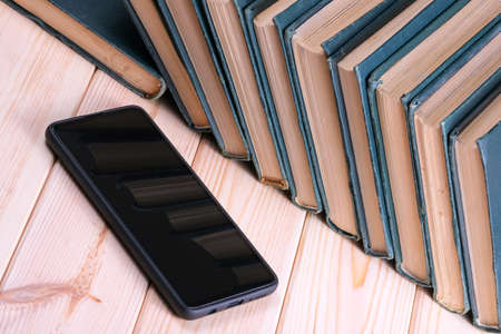 A stack of old tattered books in identical green bindings lies on a wooden table next to a black smartphone close-up