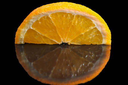 Slice of ripe sweet orange in carbonated juice on black close-up macro photography artistic fruit background Stock Photo