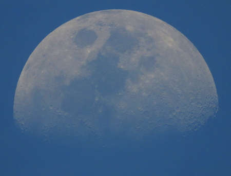 More than half of the blue moon isolated on light sky
