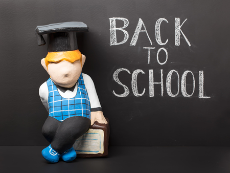 Back to school concept. Cute dummy with book on black chalkboard