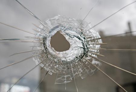 Broken glass with hole. Vandalism or violence concept