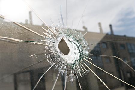 Vandalism or violence concept. Broken glass with hole