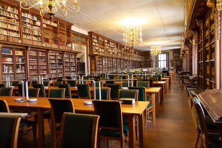 Innenraum der Universitätsbibliothek mit vielen Studententischen und Bücherregal mit alten Büchern Standard-Bild