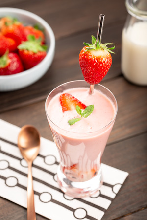 Healthy strawberry smoothie in glass on rustic wood Imagens