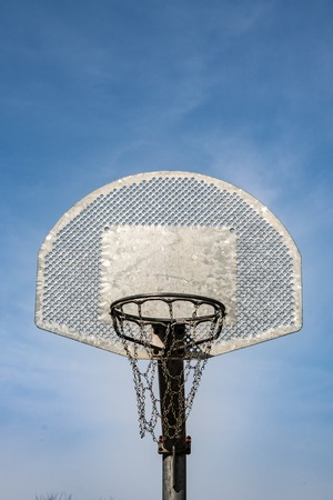Metallic basketball board and hoop with blue sky in the background