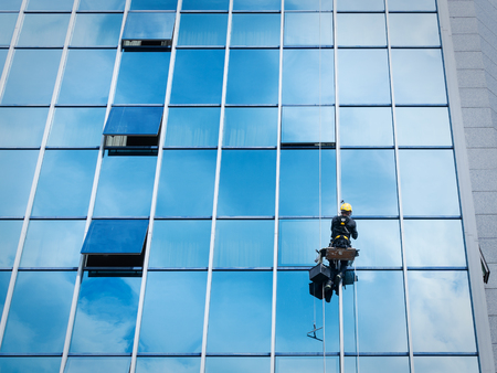 Window cleaner working on a glass facade suspended. Heavy work concept Archivio Fotografico
