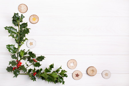 Natural Christmas background. Traditional Christmas holly with red berries on white wood background. Copy space Top view. Christmas frame Banque d'images - 122066150