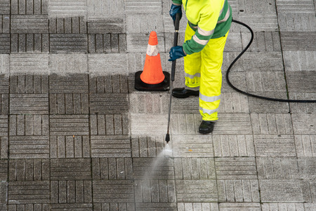 Worker cleaning the street sidewalk with high pressure water jet. Public maintenance concept 스톡 콘텐츠