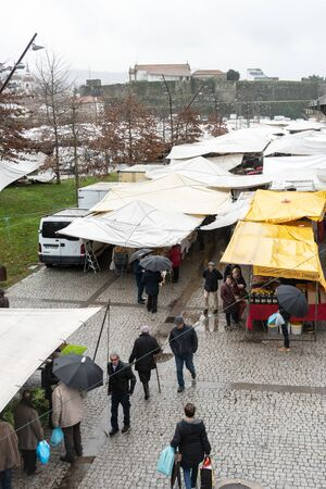 Vila nova de Cerveira, Portugal; December 15 2018: Portuguese outdoor market day on rainy day Stock Photo - 127812575