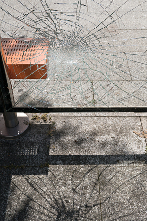 Vandalism concept. Damaged glass at bus stop shelter. Social problems Stock Photo