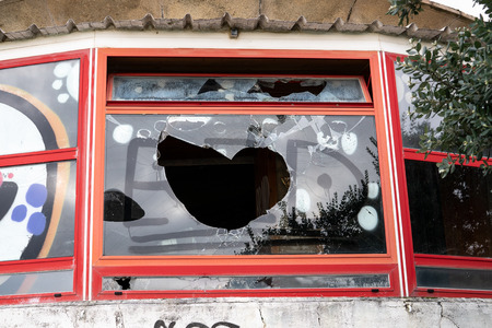 Vandalism concept. Building with Broken window and graffiti. Vandal graffiti on the window of a house