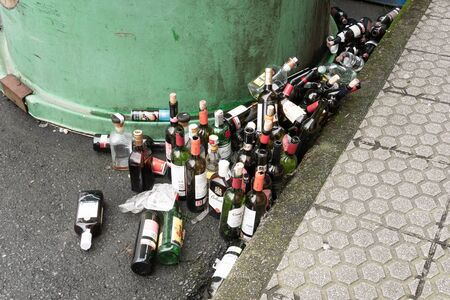 Galicia, Spain; march 8 2019: Lots of empty glass bottles near a glass container. Recycling concept