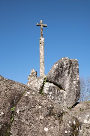 Antique stone cross on big granite rocks with blue sky. Pilgrimage, Padron, Spain