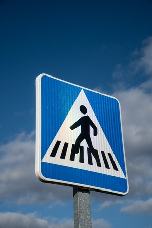 New crosswalk road sign on blue sky background. Stock Photo