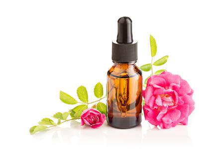 Huile essentielle de rose dans une bouteille en verre avec compte-gouttes sur fond blanc